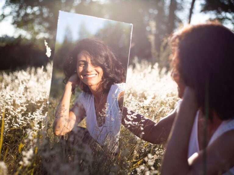 Woman looking at herself in the mirror, she is smiling because she is happy and truly loves herself